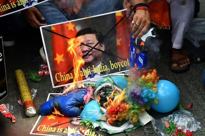 Indian activists from the right-wing organisation Hindu Sena shout anti-China slogans as they burn Chinese products during a protest in New Delhi on June 25, 2016. India has blamed regional rival China for blocking its entry to the Nuclear Suppliers