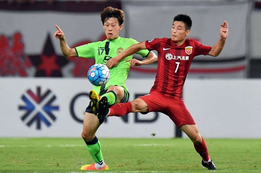Lee Jae Sung of South Korea's Jeonbuk Hyundai (left) fights for the ball with Wu Lei of China's Shanghai SIPG during their AFC Champions League quarter-final football match in Shanghai on Aug 23, 2016.