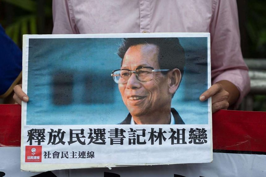 A supporter holds a photo of jailed former Wukan village chief Lin Zuluan outside the China Liaison Office in Hong Kong on Sept 9, 2016.