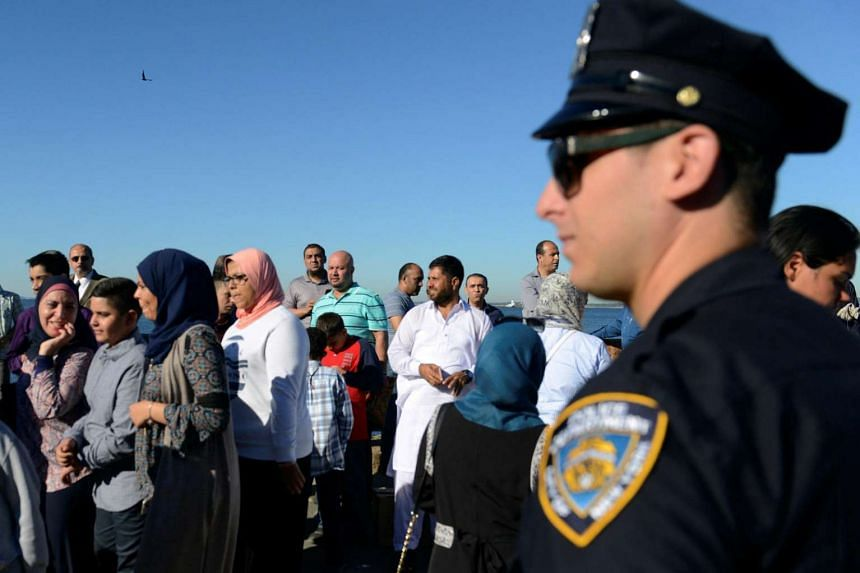 A member of the New York City Police Department stands guard during a group prayer session for the Eid al-Adha holiday in the Brooklyn borough of New York City.