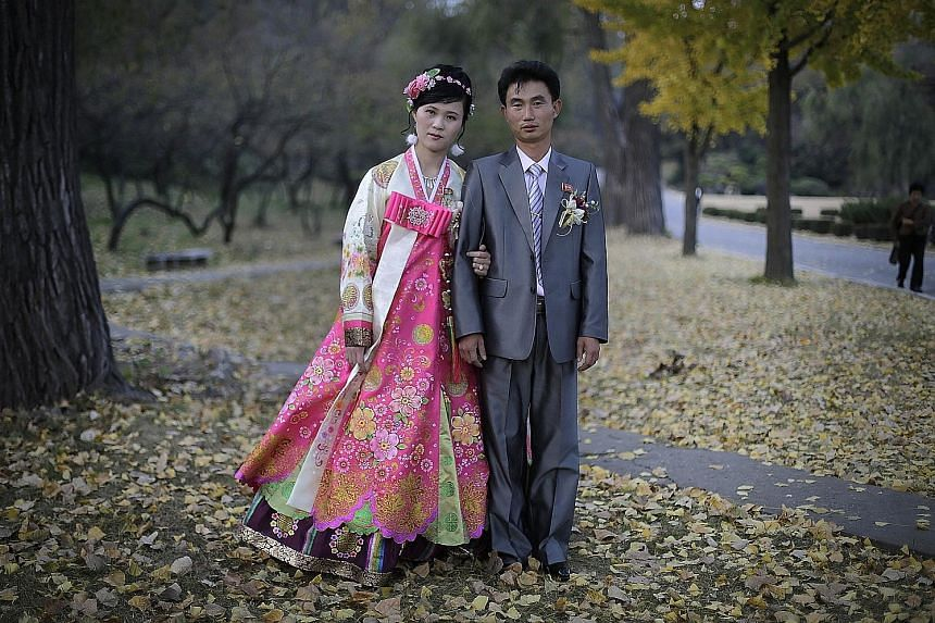 A bride and groom posing for a wedding photograph at Moranbong hill in 2014.