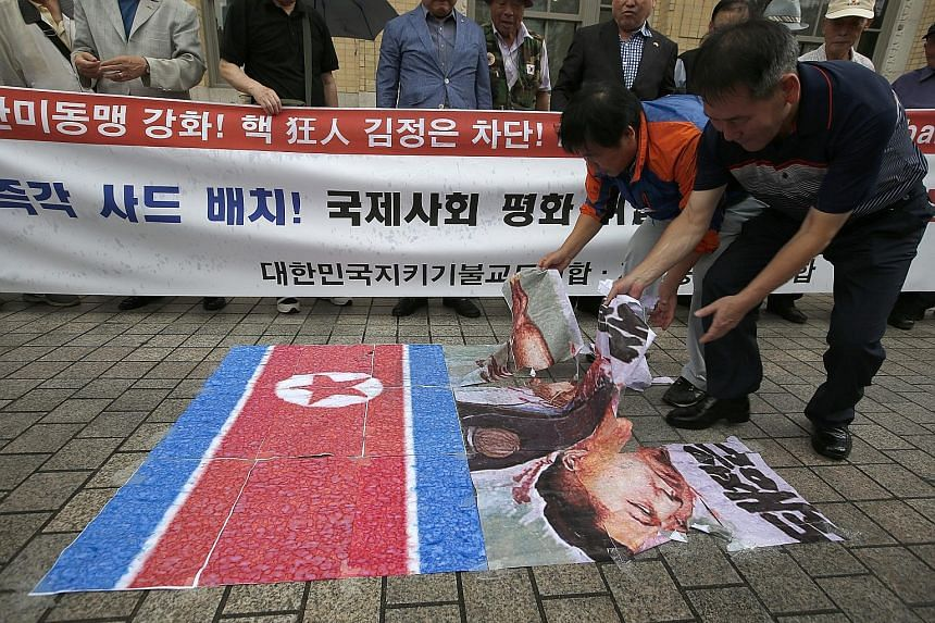 "Demonstrators in Seoul yesterday with placards that read ""Down with Kim Jong Un, Eliminate North Korean nuclear programme!"". The North's latest nuclear test has drawn widespread condemnation. South Korean protesters in Seoul yesterday tearing up post"
