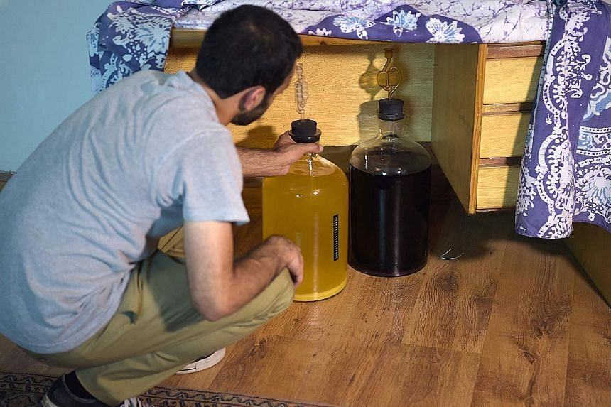 A Pakistani resident keeping bottles of homemade whisky out of sight, under a table at his home in Islamabad.