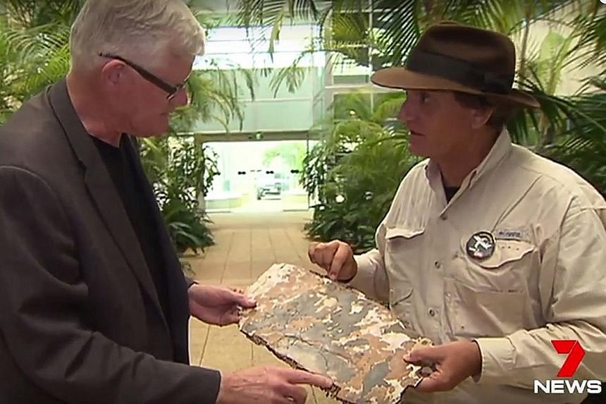 Mr Gibson (at right) seen in a screen grab of a 7News broadcast showing a piece of debris to Mr Geoffrey Thomas, the West Australian Aviation Editor.