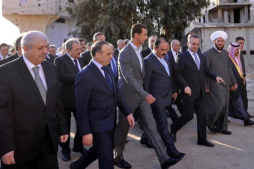 Syrian President Assad (centre) touring Daraya after performing Eid al-Adha prayers there yesterday. Daraya, a Damascus suburb long held by rebels, was recaptured by government forces last month.