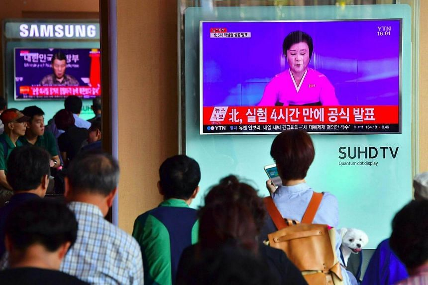 People watch a television news broadcast showing a North Korean anchor announcing the country's latest nuclear test, at a railway station in Seoul on Sept 9, 2016.