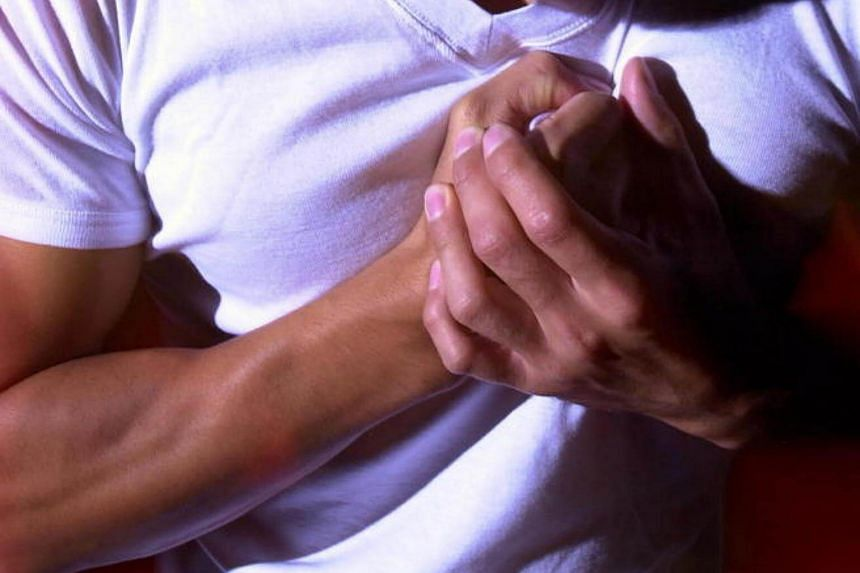 Posed photo of a man having chest pain.