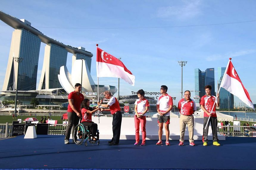 Para-swimmer Yip Pin Xiu (second from left) and shuttler Derek Wong (right) receiving the national flags prior to the 2016 Olympic and Paralympic Games, on July 9, 2016.