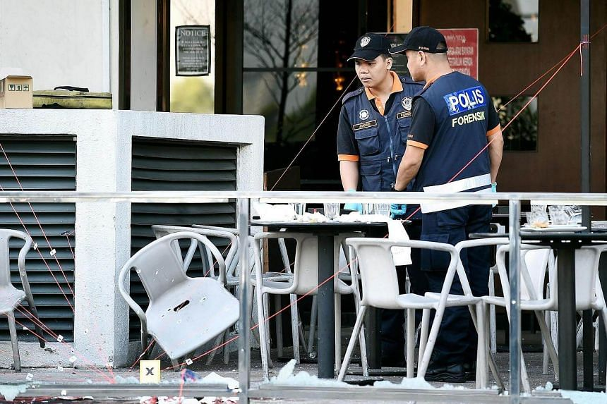 Malaysian police inspect the site of an ISIS grenade attack at a restaurant in Puchong district outside of Kuala Lumpur on June 28, 2016.