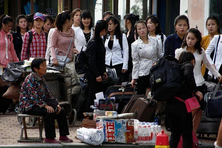 North Koreans line up outside the customs office in China's Dandong, Liaoning province on Sept 12, 2016.