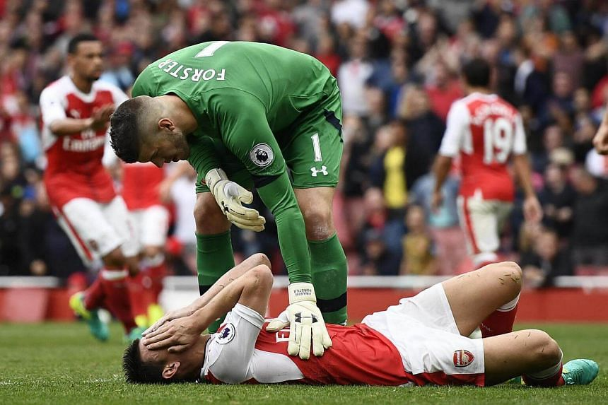 Arsenal's Laurent Koscielny lies injured as Southampton's Fraser Forster checks on him during their match on Sept 10, 2016.