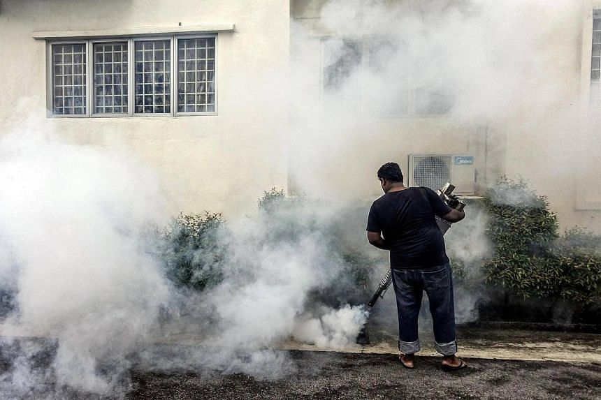 A worker spraying pesticide at an apartment block area in Kuala Lumpur, Malaysia, on Sept 8, 2016.