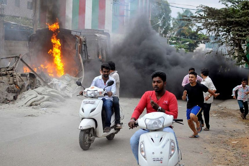 Men make their way past a burning lorry in Bengaluru, which was set on fire by protesters on Monday (Sept 12) over a river water dispute.