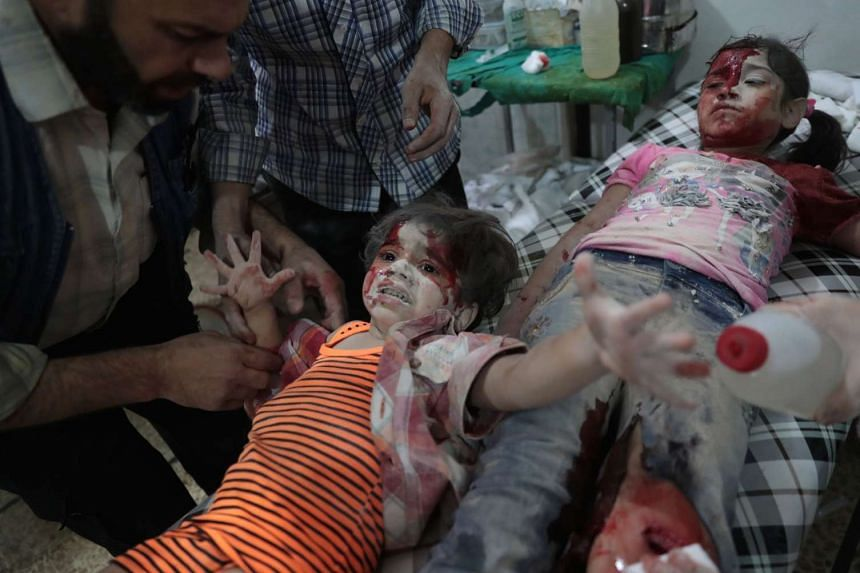 A Syrian girl reacts in pain as a wounded child lies next to her at a make-shift hospital following reported government air strikes on the rebel-held town of Douma, east of the capital Damascus on Sept 12, 2016.