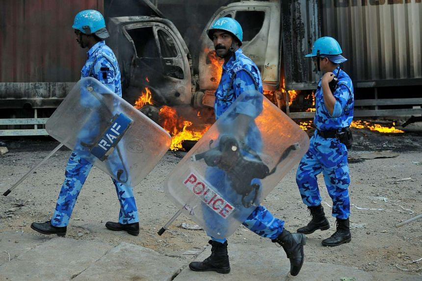 Members of the security forces make their way past burning lorries in Bengaluru, which were set on fire by protesters.