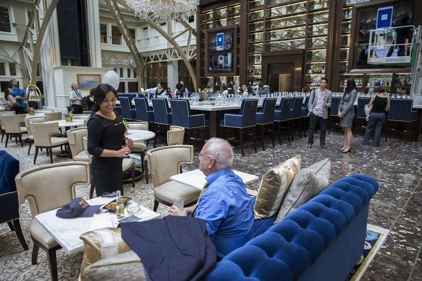 A guest talks with a server in the lobby of the Trump International Hotel just after it opened in Washington, DC on Monday (Sept 12).