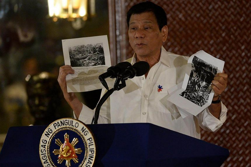 Philippine President Rodrigo Duterte holds up a photo and cites accounts of US troops who killed Muslims during the US's occupation of the Philippines in the early-1900s, during a speech at the Malacanang palace in Manila on Sept 12.