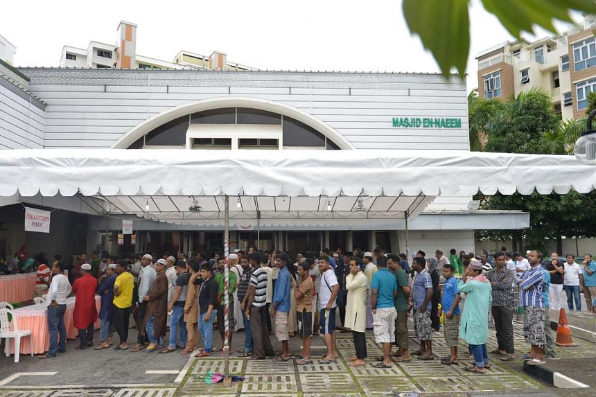 Worshippers stand in line outside En-Naeem Mosque after registering to collect korban meat. The meat was chopped and packed into bags at the mosque. Foreign workers eachreceived half a kilogram of meat, while needy families received 3kg.