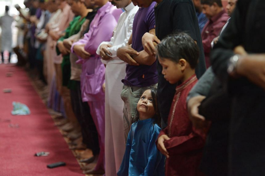 A young boy watches as worshippers say morning prayers at the En-Naeem Mosque in Hougang.