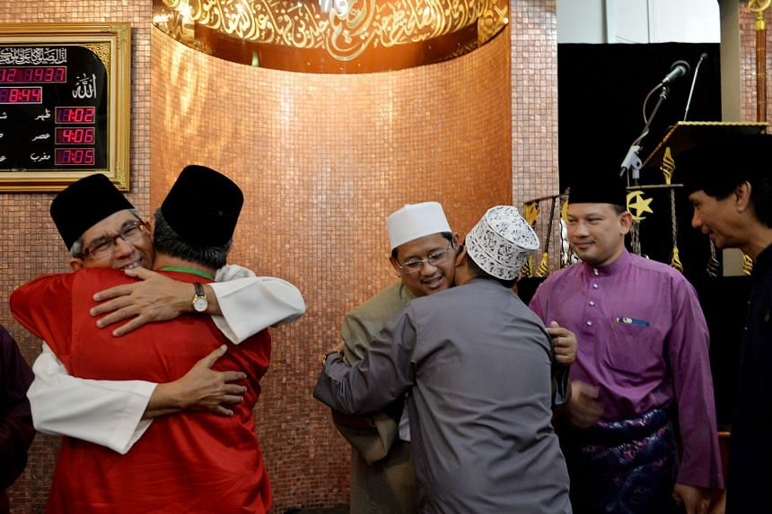 (Facing camera, from left) Dr Yaacob and the Mufti of Singapore, Dr Mohamed Fatris Bakaram, greet worshippers after morning prayers at the mosque.