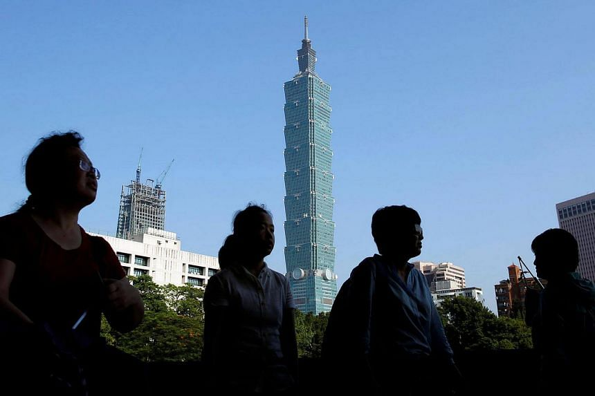 People walk past Taiwan's landmark building Taipei 101 in Taipei. A third of Taiwan's adults still live with their parents according to the latest statistics from Taiwan's Ministry of Interior.