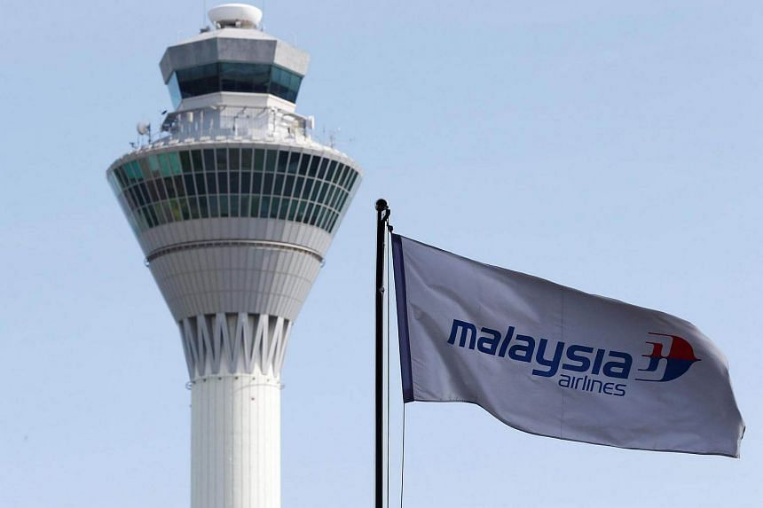 A Malaysian Airlines flag flies in front of the traffic control tower at Kuala Lumpur International Airport in Sepang.