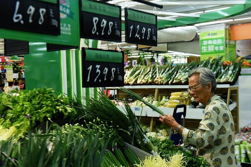 A customer selects vegetables at a supermarket in Hangzhou, Zhejiang province, China on Sept 9, 2016.  Investment in China's economy is stabilising and consumption is improving, a spokesman for China's statistics bureau said on Tuesday (Sept 13).