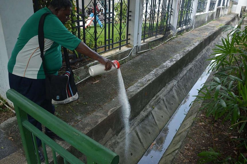 NEA officers putting granular pesticides in stagnant water in Siglap on Sept 8, 2016.