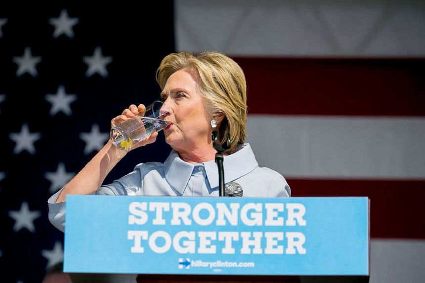 Hillary Clinton, the Democratic presidential nominee, takes a drink of water after coughing at the 11th Congressional District Labor Day Parade and Festival in Cleveland, on Sept 5, 2016.