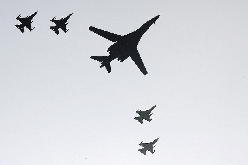 One of two B-1 bombers deployed by the US and four South Korean F-15K fighters flying over Osan Air Base in Pyeongtaek, South Korea.