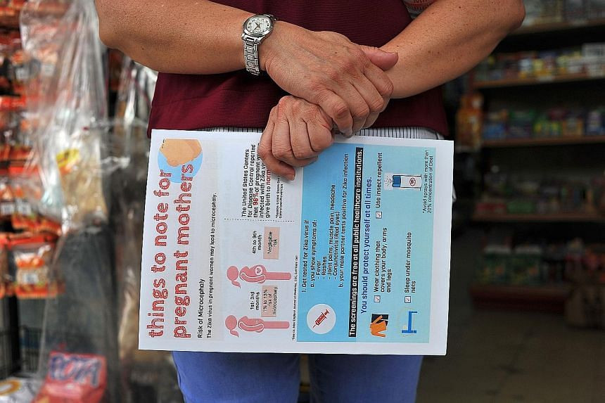 A volunteer holding an information sheet on Zika and pregnant women at a walkabout where fliers on the virus were distributed in Pasir Ris earlier this month. The Health Ministry is offering free testing to pregnant women with Zika symptoms or whose