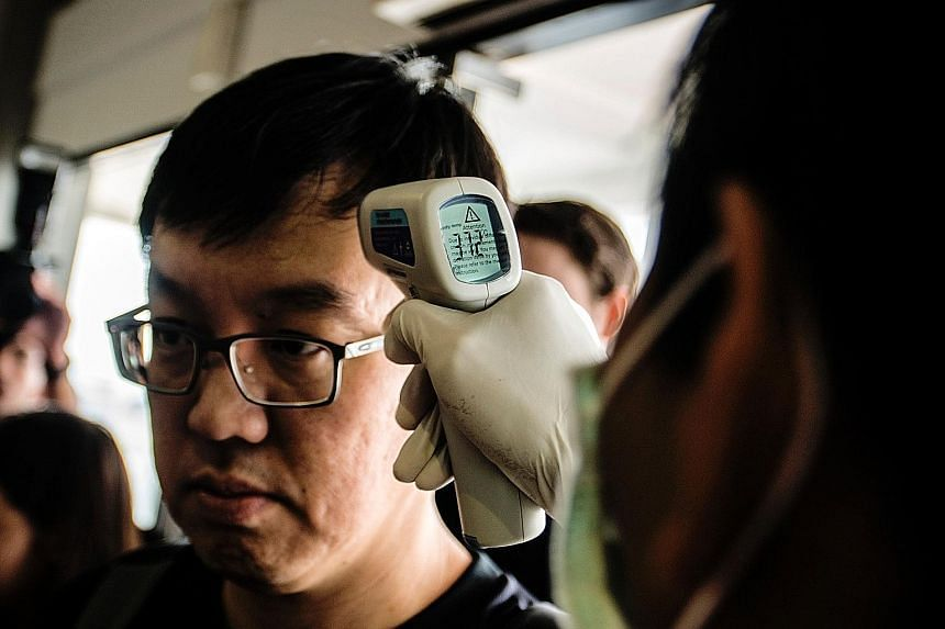 A health official at Yogyakarta airport checking the temperature of a passenger arriving from Singapore on Sept 2, after Zika cases were reported in the Republic.