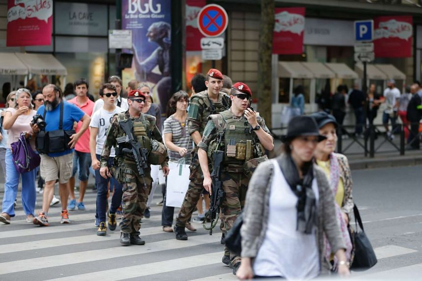 """French soldiers, part of """"Operation Vigipirate"""", patrol near the Galeries Lafayette in Paris on July 15, 2016, a day after the attack in Nice."""