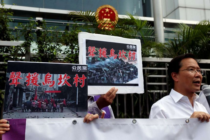 """Protesters demonstrate with placards which read """"Support Wukan village"""" outside China Liaison Office in Hong Kong on Sept 14, 2016."""