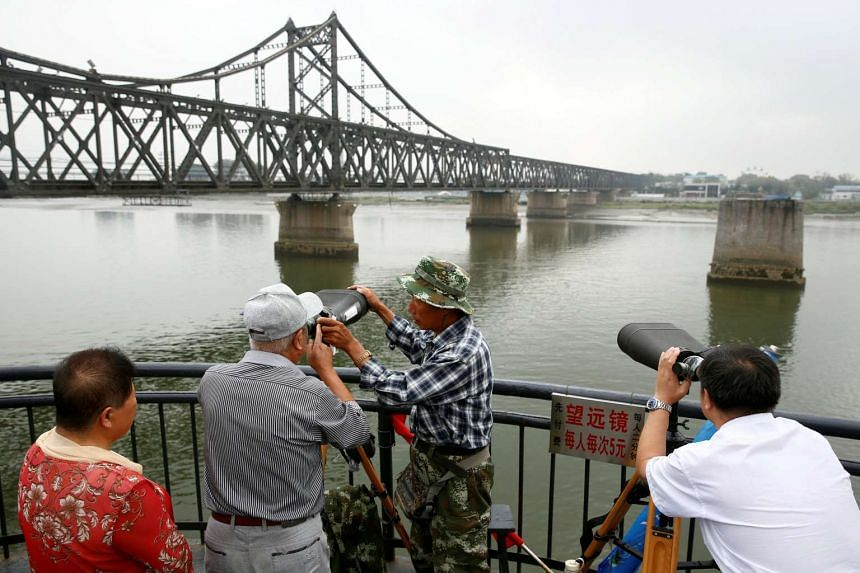 People look through binoculars towards North Korea from a destroyed bridge that once linked North Korea's Sinuiju and Dandong in China's Liaoning province.