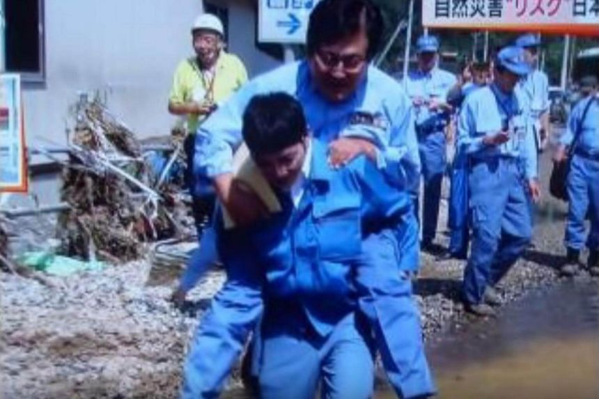 Mr Shunsuke Mutai being carried across a large puddle of water.