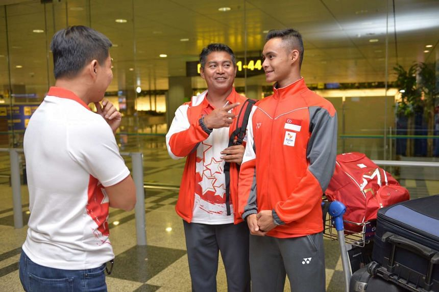 Long jumper Suhairi Suhani (centre) and his coach Muhammad Hosni (left) arrive home from the 2016 Rio Paralympics on Sept 14, 2016.