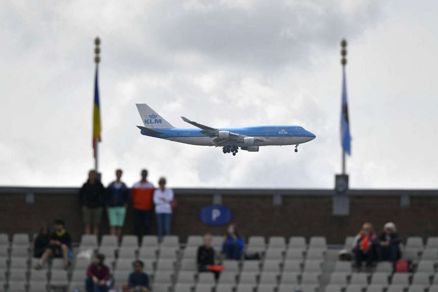 A KLM commercial plane lands at Shipol airport behind spectators watching the European Athletics Championships on July 6, 2016.