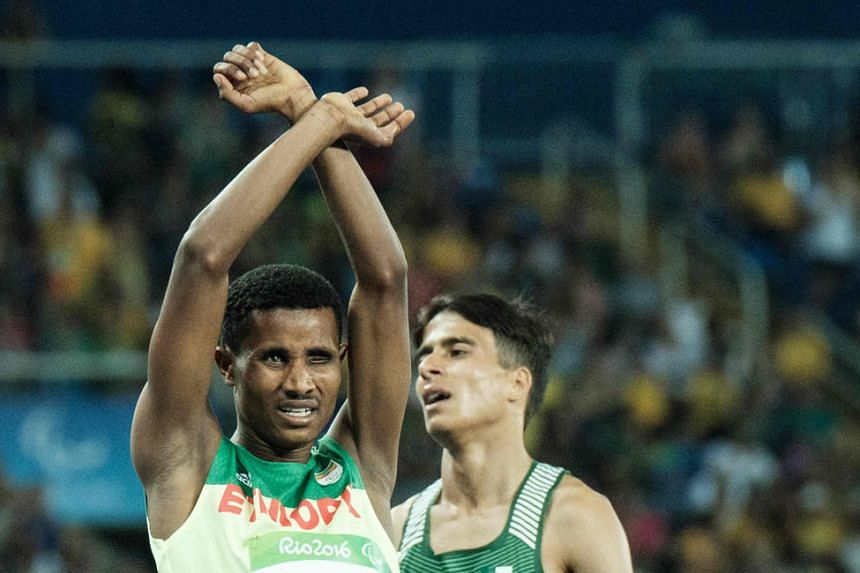 Ethiopia's Tamiru Demisse, silver medallist in the men's T13 1,500m, crosses his arms in a symbol of defiance against the country's government.
