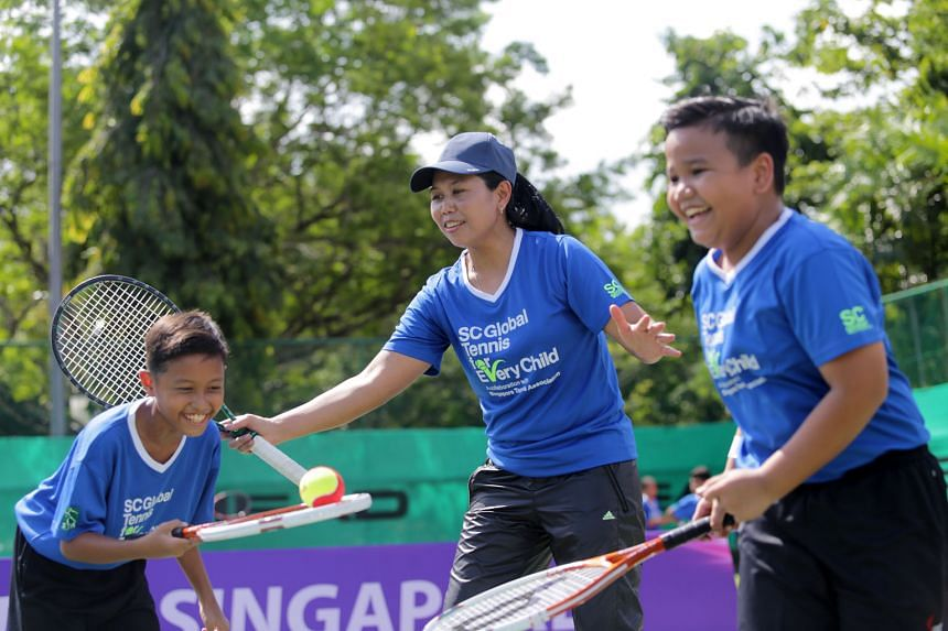 Former world No. 19 Yayuk Basuki (centre) with students Muhammad Rasul (left) and Zakir Zulkarnain (right) at a tennis clinic yesterday. The clinic, featuring 36 children from five primary schools, is part of the SC Global Tennis for Every Child Inter-Sch