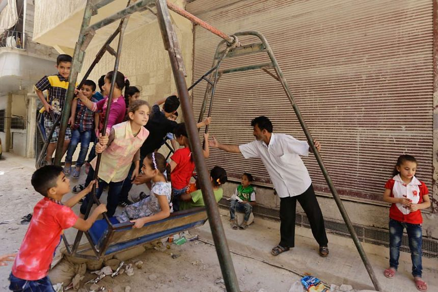 Syrian children play on a street in a residential suburb of the Syrian capital Damascus on Sept 13, 2016.