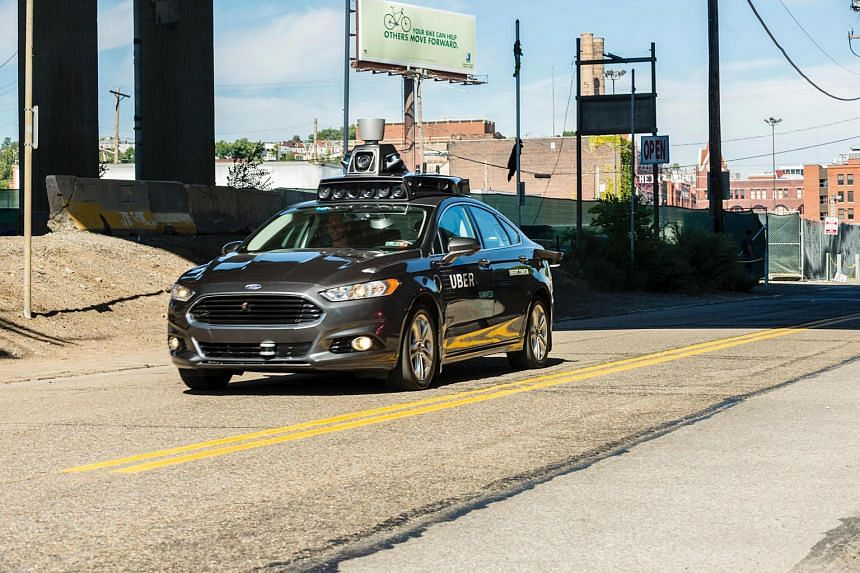A passenger look on as he rides in a pilot model of an Uber self-driving car on Sept 13, 2016 in Pittsburgh, Pennsylvania.