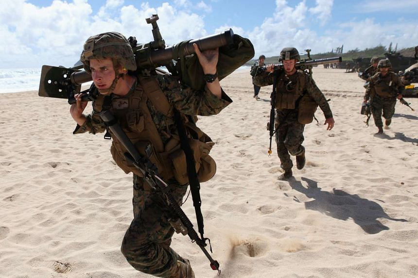 Marines run down the beach to set up a mortar defense during a simulated beach assault at Marine Corps Base Hawaii with the 3rd Marine Expeditionary Unit in Kaneohe, Hawaii.