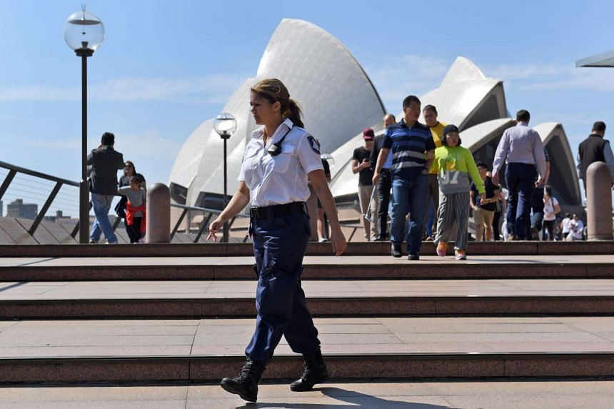 A security guard patrols the forecourt of the Sydney Opera House after a man was charged for making threats at the Sydney Opera House.