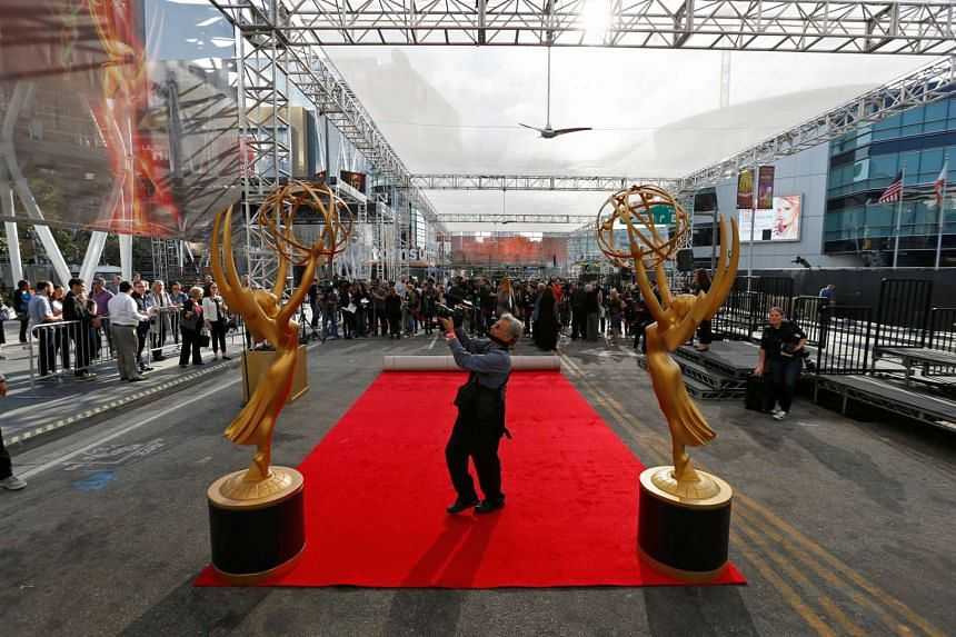 A member of the media is pictured between two Emmy statues during preparations for the 68th Emmy Awards at Microsoft Theater in Los Angeles, California.