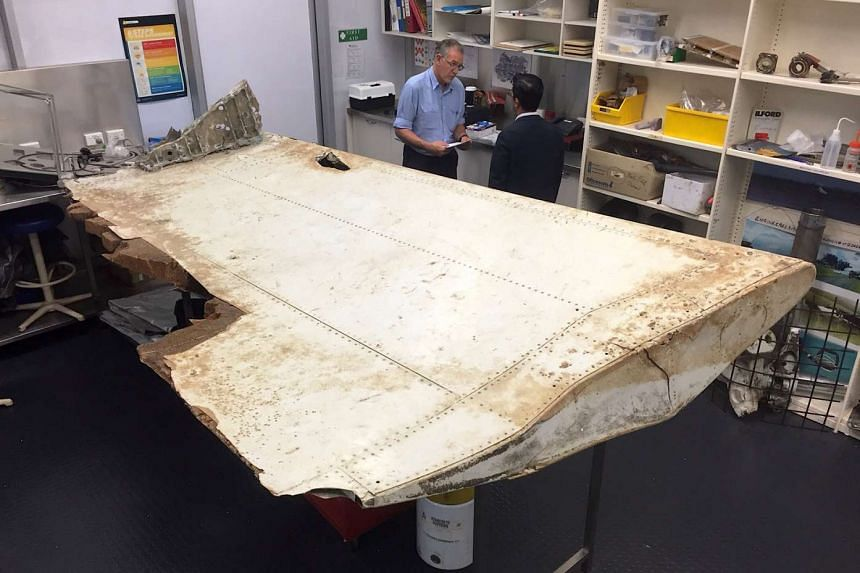 Australian and Malaysian officials examine aircraft debris found near Tanzania at the Australian Transport Safety Bureau headquarters in Canberra on July 20, 2016.