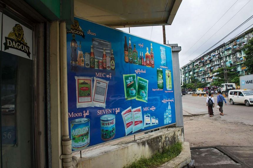 A poster displays beer, liquor, beverage, rice, sugar, milk and bottled water products made by the Myanmar Economic Cooperation outside a store in Yangon on Sept 15, 2016.