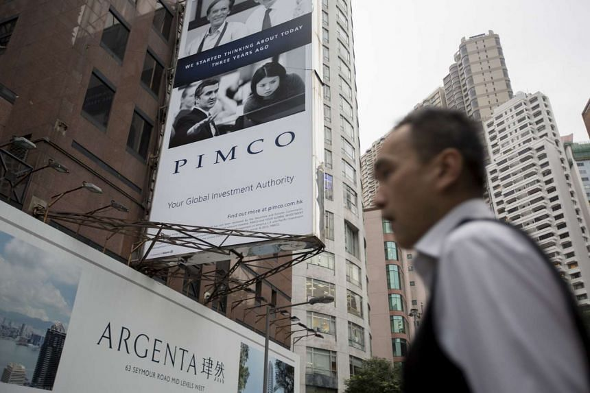 A man walks past a Pimco advertisement which is displayed on a building in Hong Kong.