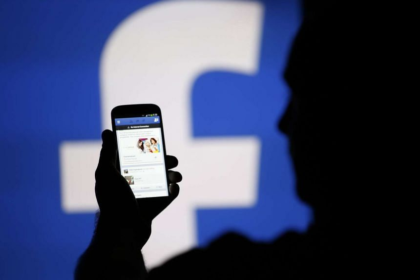 A man is silhouetted against a video screen with an Facebook logo.