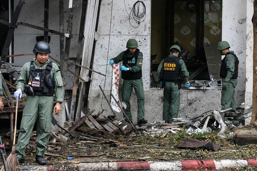 A Thai bomb squad inspects the site of a deadly bombing in the southern province of Pattani.